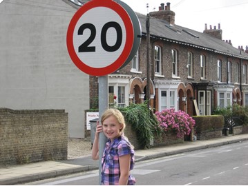 Girl next to a 20mph road sign