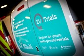 Rear of an electric van with an advert for the Highways England EV trial