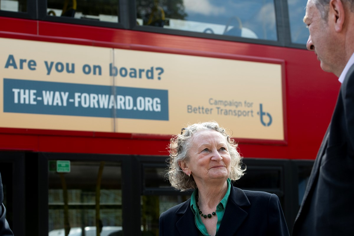 Jenny Jones, Baroness Jones of Moulsecoomb, talking to Norman Baker from Campaign for Better Transport beside a campaign-branded double-decker bus
