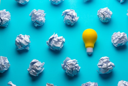 lightbulb among crumpled paper