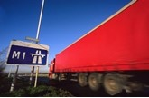 Red longer goods vehicle driving past M1 motorway sign