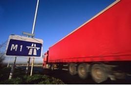 Red longer goods vehicle driving past M1 motorway sign