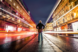 Man standing in middle of wet shopping street with headlight trails either side of him
