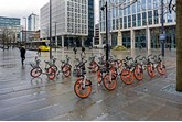 View of Manchester vity bikes. The bikes can be seen parked ready for use. A tram can be seen leaving the ttram station and people can be seen walking on the pavements.