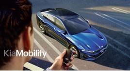 Man pointing a car key at a blue car with Kia Mobility logo