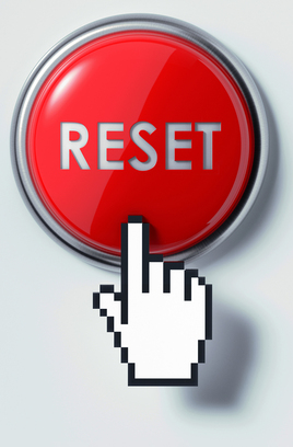 Mouse hand hovering over the computer reset button