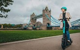 Girl on a Tier e-scooter in front of Tower Bridge in London
