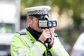 Police officer holding radar speed gun