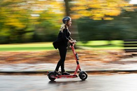 Woman on a Voi e-scooter