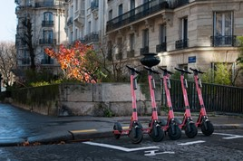 Row of Voi scooters in front of building