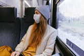Female passenger on a train wearing a white face mask